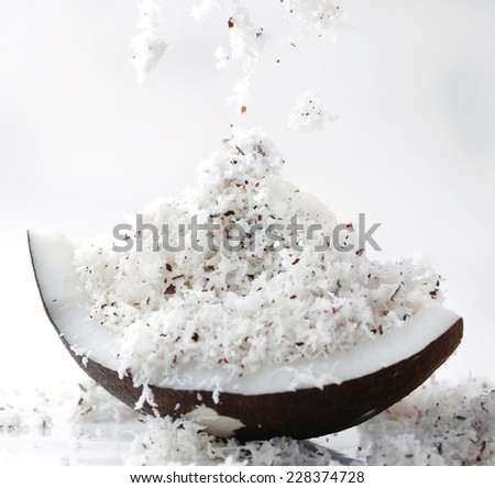 Ssprinkle grated coconut on coconut - stock photo