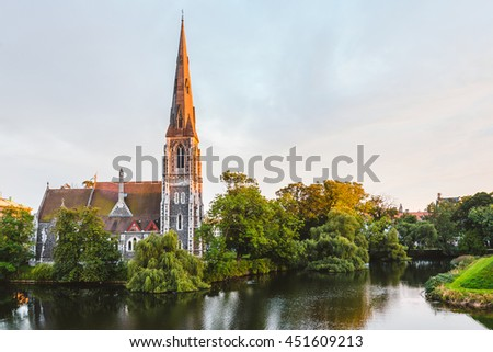 St. Alban's Church colored in gold by setting sun and reflected on water of pond. Golden hour on Copenhagen, Denmark.
