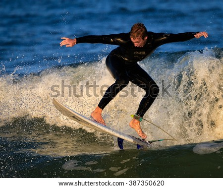 St. Augustine, FL - FEB 17 - Surfer rides the waves at sunset in St Augustine, FL - stock photo