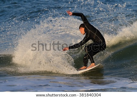 St. Augustine, FL - FEB 17 - Surfer rides the waves at sunset in St Augustine, FL on Feb 17, 2016 - stock photo