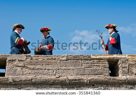ST. AUGUSTINE, FLORIDA - NOVEMBER 21: Actors dressed up in original period costumes firing cannons in Castillo de San Marcos for tourists on November 21, 2010 in St. Augustine, Florida, USA. - stock photo