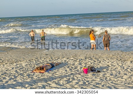 ST. AUGUSTINE, USA - JULY 23, 2010: people enjoy the beautiful beach in St. Augustine, USA. St. Augustine, Florida, was founded in 1565 and beside the historical sites famous for its beaches. - stock photo