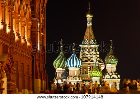 St. Basil's Church in Red Square, Moscow at Night with crowds walking around. View as seen from the State Historical Museum. - stock photo