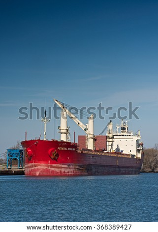St. Catharines, Ontario, Canada - November 25, 2015: The Federal Kivalina lake freighter discharging cargo at Port Weller on the Welland Canal.