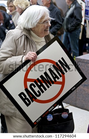 ST. CLOUD, UNITED STATES - OCTOBER 30: An elderly voter carries a sign symbolizing opposition to incumbent U.S. Rep. Michele Bachmann on October 30, 2012 in St. Cloud. - stock photo
