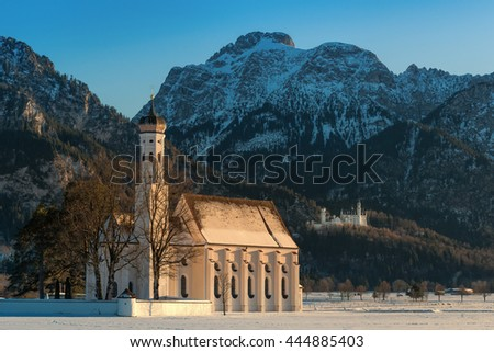 St. Coloman church together with the Neuschwanstein castle at sunset on a sunny winter day with snow and frost; Fussen, Bavaria, Germany