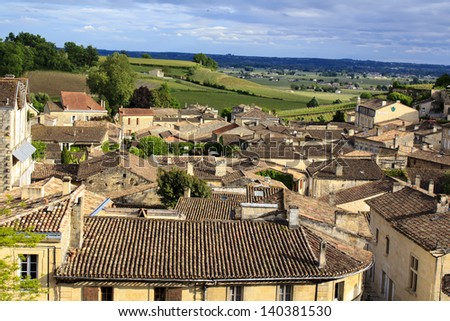 St-Emilion roofs - several sun beams struggling throuth heavy rainy clouds. It is one of the main red wine production areas of Bordeaux region. The town is a UNESCO World Heritage site. - stock photo
