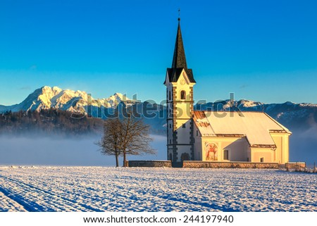 St. Florian church with a view to the alps in the morning on a field near Menges, Slovenia - stock photo