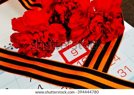 St George ribbon and red carnations above the calendar with 9th May date - the day of victory in Great Patriotic War in Russia. 9 May concept.  - stock photo