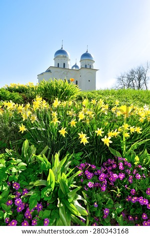 St. George's Cathedral, Russian orthodox Yuriev Monastery in Veliky Novgorod, Russia - spring architectural landscape with flowers - stock photo