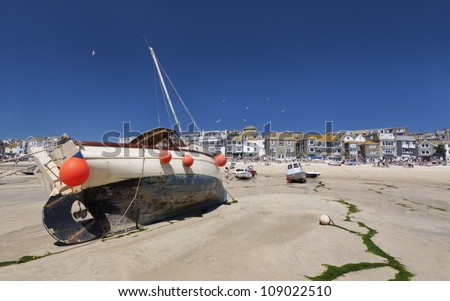 St Ives Harbour in Cornwall, England. Summer time. Taken at Low tide. Seaside properties, fishing boats and tourists. - stock photo
