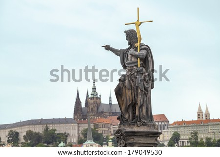 St. John the Baptist, is shown as a preacher with a golden cross and a font from a shell on his side.  Sculpted by Josef Max in 1857 in the Charles Bridge, Prague, Czech Republic - stock photo