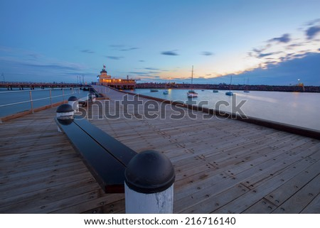 St. Kilda Pier at Dusk with boats in the harbour, and Pavilion in the distance. - stock photo