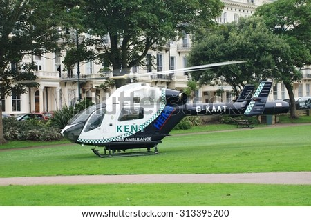 ST. LEONARDS-ON-SEA, ENGLAND - AUGUST 27, 2015: The Kent Air Ambulance lands in Warrior Square Gardens while attending a medical emergency. The helicopter is a McDonnell Douglas MD902 Explorer. - stock photo