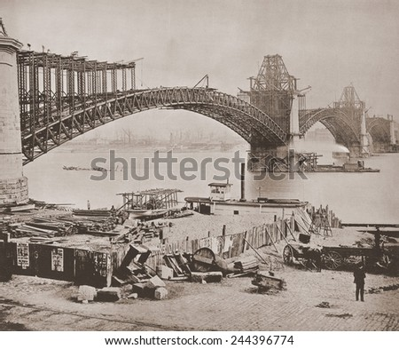 St. Louis Bridge under construction ca. 1870. The steel arches were cantilevered from opposing piers high above the river. The bridge's scale materials and design were unprecedented. - stock photo