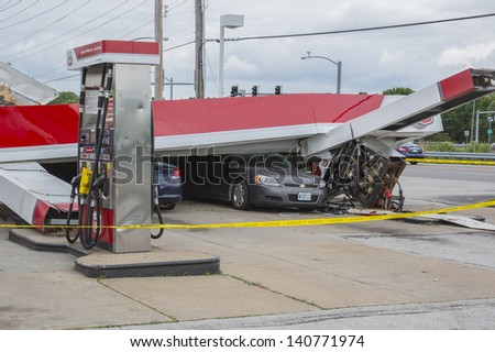 ST. LOUIS - MAY 31, 2013: Cars and homes were heavily damaged by a tornado that swept through Florissant Missouri in the suburbs of St. Louis on, May 31, 2013.This gas station had roof fall on cars.