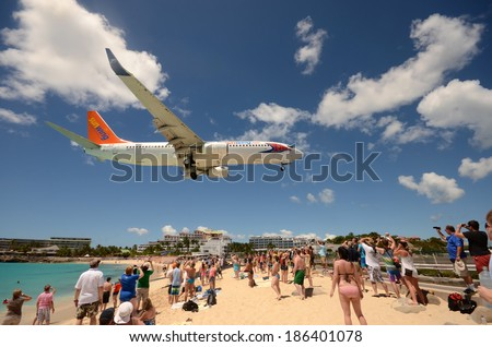 ST MAARTEN - MARCH 27: Beach crowds observe low flying airplanes landing near Maho Beach on the island of St Maarten in the Caribbean on March 27, 2014. it a favorite place to visit on the island - stock photo