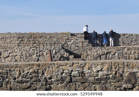 ST MICHAEL'S MOUNT, UK - OCTOBER 31, 2016. Visitors on the harbour wall at St Michael's Mount, a small tidal island accessed by a causeway from  Marazion, in Cornwall, southwest England, UK.