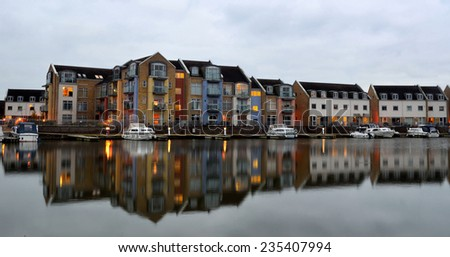 ST NEOTS, CAMBRIDGESHIRE, ENGLAND - NOVEMBER 30, 2014: Marina apartments Eynesbury St Neots. New marina built on the River ouse. Photo taken early evening with lights and reflection.