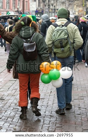 St. Patrick day-young man and girl in clothes of celebratory color easy walk on city