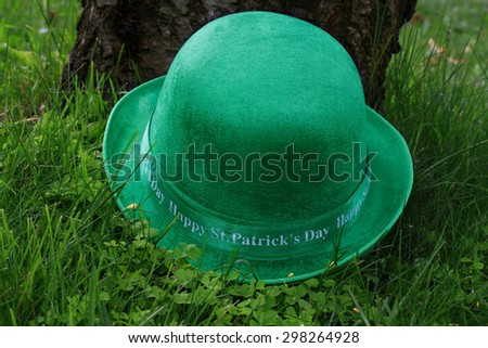 St. Patrick?s Arrangement - green men hat (derby hat), over clover (shamrocks) and grass in front of cherry tree