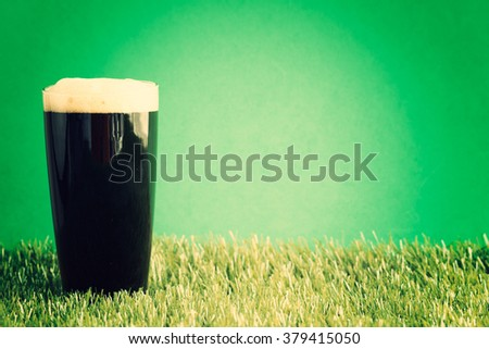 St. Patrick's Day Beer glass over grass and green background - stock photo