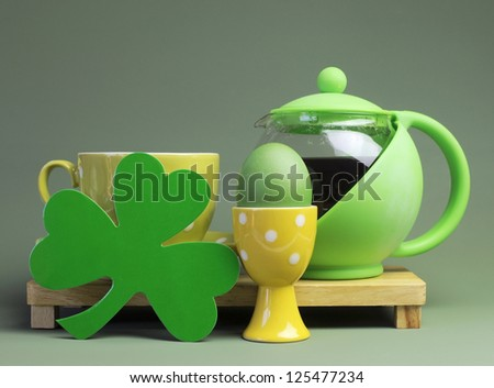 St Patrick's Day breakfast with green pot of tea, tea cup and saucer with shamrock, against a green background. - stock photo