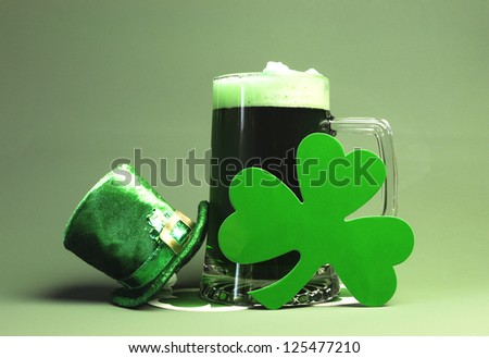 St Patrick's Day green beer with shamrock and Leprechaun hat against green background. - stock photo
