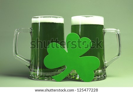 St Patrick's Day green beers with shamrock against green background. - stock photo