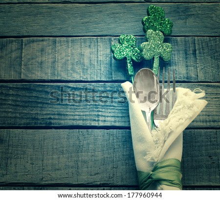 St. Patrick's Day Green Shamrocks and Silverware with white Napkin on Rustic Wood Background with room or space for copy, text, words.  Vintage camera instagram treatment. - stock photo