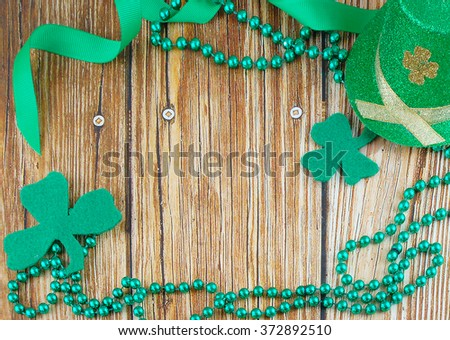 St. Patrick's Day image of green beads and ribbon and shamrock shapes cut out of felt with a sparkly leprechaun's hat added are creating a border around a rustic wooden background. Copy space center. - stock photo