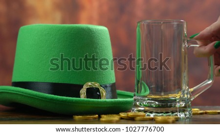 St Patrick's Day pouring green beer with green leprechaun hat and gold covered chocolate coins against rustic wood background