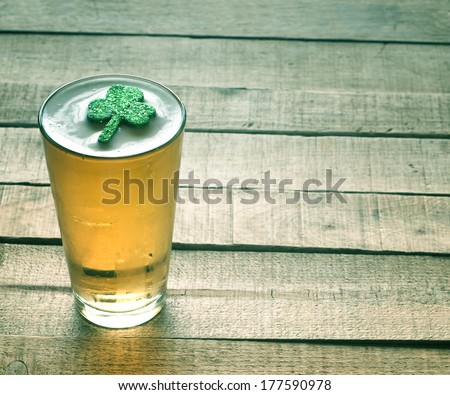 St. Patricks Day green shamrock floating in a cold, frosty glass of beer on a rustic wood background with room or space for copy, text, words.  Vintage camera instagram treatment for mood effect.   - stock photo