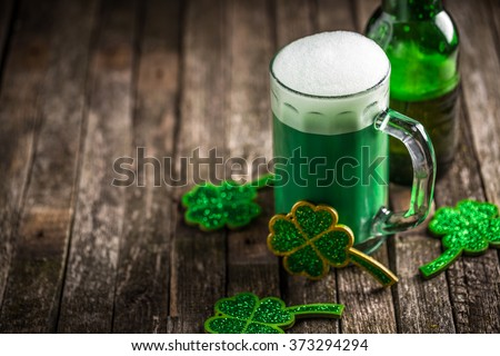St. Patricks Day green shamrocks with a full cold frosty glass of beer - stock photo