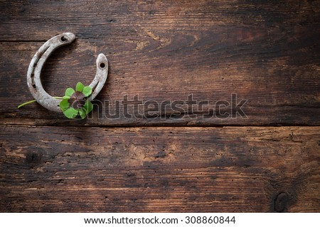 St.Patricks day, lucky charms. Four leaved clover and a horseshoe on wooden board - stock photo