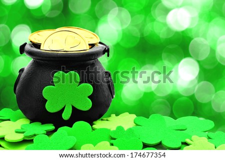 St Patricks Day Pot of Gold and shamrocks over a green background - stock photo