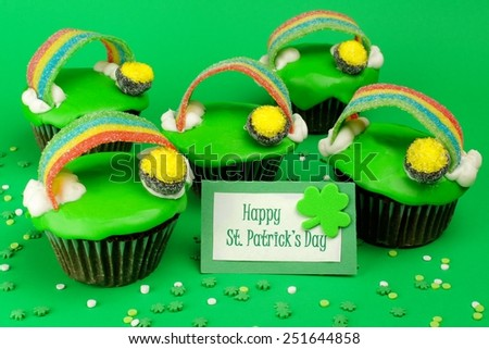 St Patricks Day rainbow, pot of gold cupcakes with greeting card on a green background - stock photo