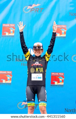 ST. PAUL, MINNESOTA - JUNE 15, 2016: Pro cyclist Lauren Stephens atop winner's podium at North Star Grand Prix time trial in St. Paul on June 15 as she accepts the black jersey for Best Sprinter.  - stock photo