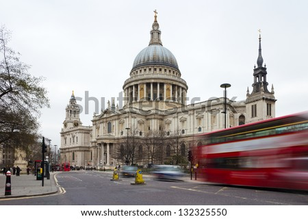 St Paul's Cathedral in London. Day shooting with slow shutter speed so that red dabldekker London cabs and blurred by movement - stock photo