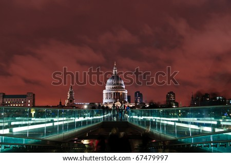 St Paul's Cathedral standing out in front red clouds. Shooting from the Millennium Bridge with people standing on it.