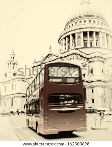 St. Paul's Cathedral with red bus in London sepia vintage effect - stock photo