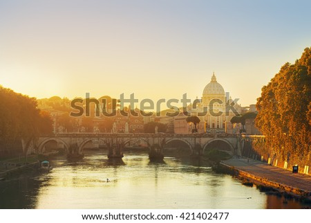 St. Peter's cathedral over bridge and river in Rome at sunset, Italy