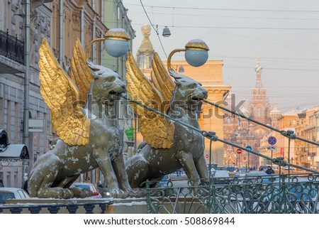 St. Petersburg in the winter. griffin sculptures with gold wings on the Bank bridge on the background of the city's architecture