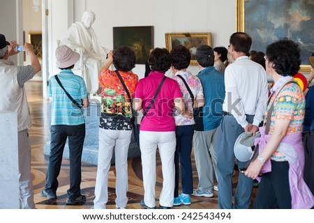 ST. PETERSBURG - JUNE 30, 2011: Unidentified  tourists photograph the statue Voltaire by Houdon Jean Antoine at the Hermitage. Over 3 million people visit the museum every year. - stock photo