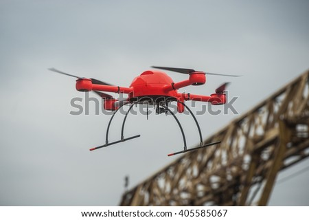 St. Petersburg, Russia - 6 April 2016: Red big powerful drone with attachments: video camera, a dosimeter, tracking devices for radiation situation flies over industrial facility.