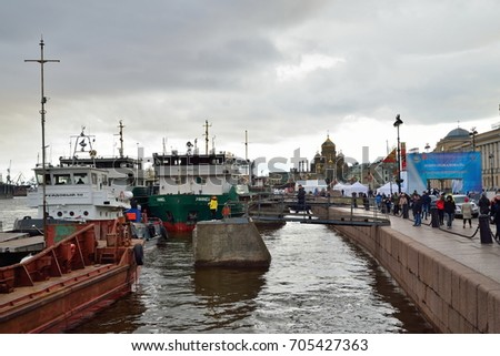 ST.PETERSBURG, RUSSIA - APRIL 30, 2017:  Tugboat Reydovy-50, and barge Utimes moored at the Lieutenant Schmidt embankment in Saint-Petersburg under the clouds.