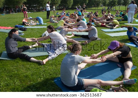 St. Petersburg, Russia - August 8, 2015: The massive free practice session of yoga for all levels of people in a city park on a day off. Activity passes of pairs people