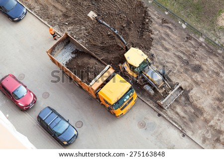 ST. PETERSBURG, RUSSIA - CIRCA APR, 2015: Communal service machinery makes urban land improvement in Russia apartment courtyard. Creation of living environment in city - stock photo