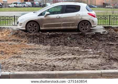 ST. PETERSBURG, RUSSIA - CIRCA APR, 2015: Vehicle is left on lawn while machinery makes urban land improvement. Russia apartment courtyard with parking lot - stock photo
