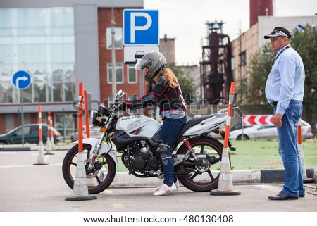ST. PETERSBURG, RUSSIA - CIRCA AUG, 2016: Driver instructor controls L-driver while she doing exercise of driving bike from parking lot. Skill training motordrome. Russian driver school